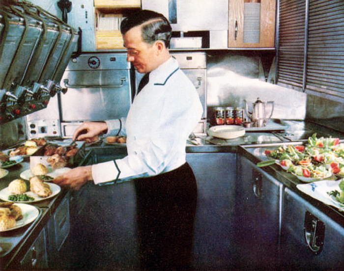 A Pan American steward prepares gourmet meals in the large Stainless-steel B-377 Stratocruiser. The galley included electric ovens and was located behind the passenger cabin on the upper deck.