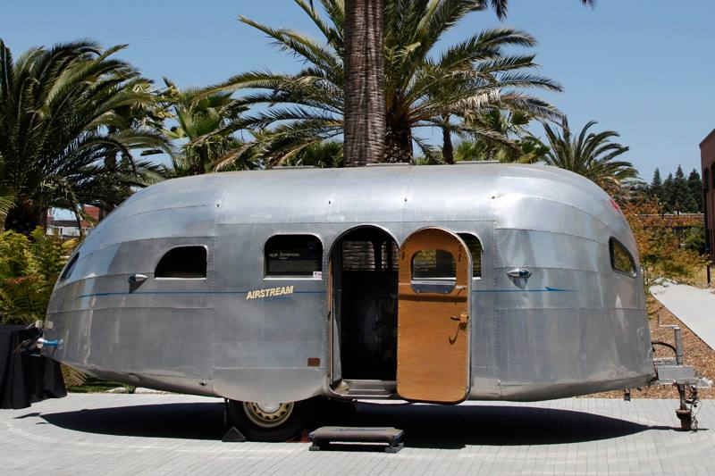 "Although a very different model than Ric's, on January 17, 1936, the Airstream Trailer Co. introduced the ""Clipper,"" named after the Pan American Clipper airplanes, and a well-known American brand was born. The Clipper with its semi-monocoque, riveted aluminum body, had more in common with the aircraft of its day than with its travel trailer predecessors. It could sleep four, thanks to its tubular steel-framed dinette which could convert to a bed. It carried its own water supply, had an enclosed galley, and was fitted with electric lights throughout. The Clipper boasted advanced insulation and a ventilation system, and even offered ""air conditioning"" that used dry ice."